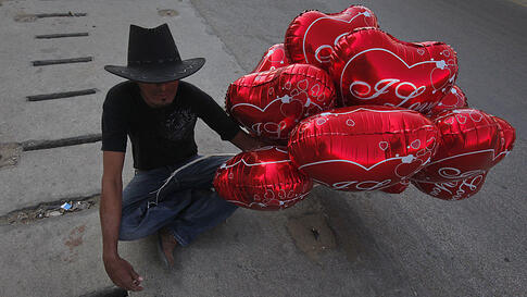 A man holds Valentine's Day balloons for sale along the roadside in Karachi, Pakistan, February 14, 2012.  (REUTERS)
