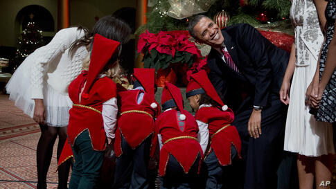 U.S. President Barack Obama laughs as children dressed like elves gathered around a Christmas tree, look at their presents presented to them by the first family at the National Building Museum in Washington, D.C., Dec. 15, 2013.