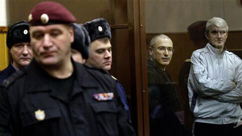 Dec. 28: Mikhail Khodorkovsky and his co-defendant Platon Lebedev, right, are seen at a court room in Moscow. Khodorkovsky's conviction for stealing oil from his own company and laundering the proceeds will likely keep the oil tycoon behind bars for sever
