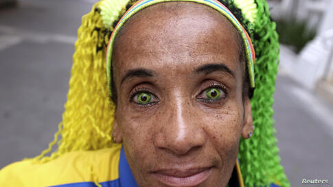 Ana Luiza, wearing contact lenses in the colours of the Brazilian national flag, poses on a street in Sao Paulo, March 23, 2014.