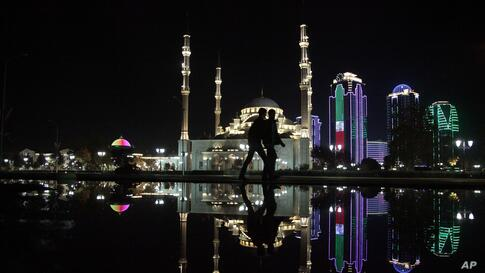 People walk in downtown Grozny, capital of Chechnya, southern Russia, as the Central Mosque is reflected in the water, Oct. 21, 2013.