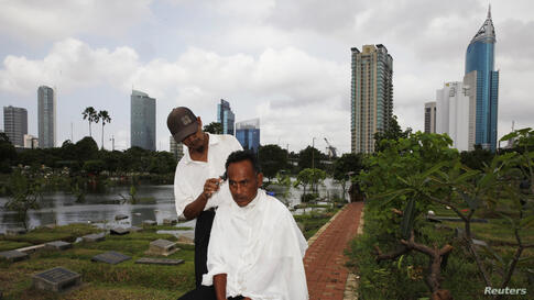 Cemetery worker Mohammad Udin has his hair cut by a mobile barber as the flooded cemetery complex is pictured in the background in Jakarta, Indonesia.