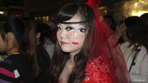 A woman who drew part of a face on her cheek, stands among the crowd at a costume party to celebrate Halloween in Wuhan, Hubei province, China, Oct. 31, 2013.