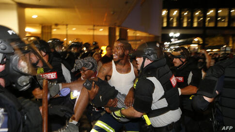 Police and protesters carry a seriously wounded demonstrator into the parking area of the the Omni Hotel in Charlotte, North Carolina, during a march to protest against the police fatal shooting of Keith Scott, Sept. 21, 2016. Scott, who was black, was...