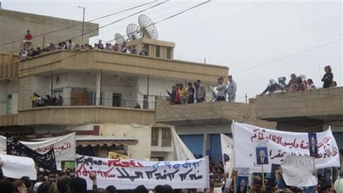 In this citizen journalism image made on a mobile phone, Syrian protesters carry banners in Arabic and Kurdish that call for a democratic nation as they demonstrate in the northeastern town of Qamishli, Syria, April 29, 2011