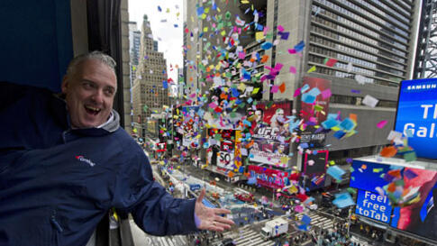 John Heald tests confetti that will be used in the New Year's celebration from a window above Times Square