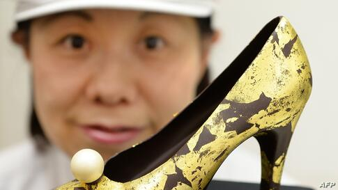 A salesclerk displays a high-heeled shoe-shaped chocolate decorated with gold leaves at the Seibu Department Store in Tokyo, Japan.