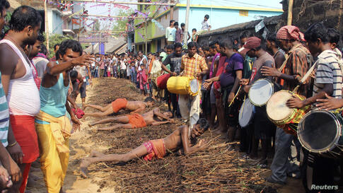 """Devotees roll on thorny bushes laid on the ground to reach a temple as they perform a ritual during the """"Danda"""" festival in Khurda district in the eastern Indian state of Odisha."""