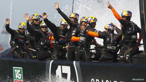 Crew from Oracle Team USA wave to fans after defeating Emirates Team New Zealand during Race 16 of the 34th America's Cup yacht sailing race in San Francisco, California, Sept. 23, 2013.