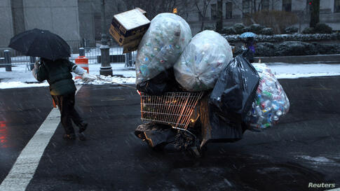A woman pulls a cart loaded with plastic bottles through falling snow in lower Manhattan in New York City. A winter storm pushed into the northeast U.S. with several inches of snow forecasted for the New York City area.
