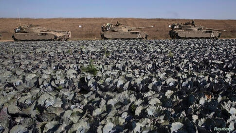 Israeli tanks stand on the edge of a cabbage field outside the central Gaza Strip.