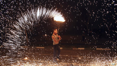 An Iranian man plays with a firework in the Pardisan Park in Tehran, Mar. 18, 2014, during Chaharshanbe Souri, or Festival of Fire. Iranians jump over burning bonfires and throw firecrackers celebrating arrival of the spring which coincides with their ...