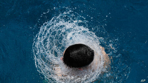 A boy dives out of the water at the Olympic open air public pool in Berlin, Germany.