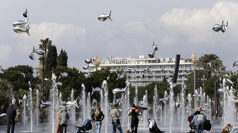 People look at fish-shaped balloons in front of water fountains in Nice on the French Riviera.