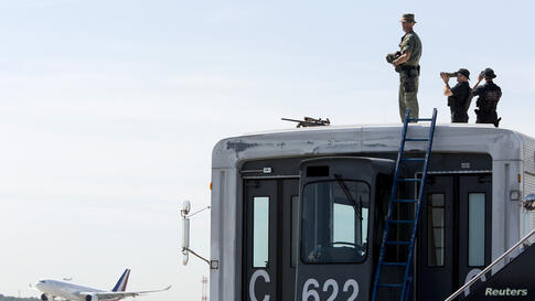 Security personnel watch as the airplane carrying French President Francois Hollande and his companion Valerie Trierweiler arrives for the G8 Summit at Dulles International Airport in Chantilly May 18, 2012.