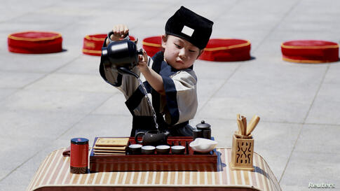 A child wearing costumes performs a tea ceremony ahead of the Dragon Boat Festival in Shenyang, Liaoning province. The festival is commemorated in memory of Chinese patriotic poet Qu Yuan, who drowned himself in 277 B.C.