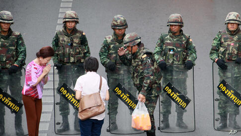 Well-wishers hand cold drinks to Thai soldiers securing the area to prevent an anti-coup demonstration at Victory Monument in Bangkok, Thailand.