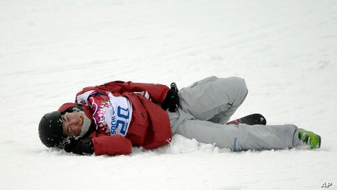 Canada's Yuki Tsubota lies in the snow after crashing during the women's freestyle skiing slopestyle final at the Rosa Khutor Extreme Park, Krasnaya Polyana, Russia, Feb. 11, 2014.