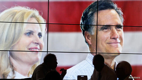 Convention goers enjoy their pizza lunch in front of a large video screen showing Mitt Romney and his wife Ann at the second session of the RNC.