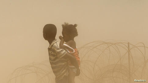 Children are engulfed in dust as a convoy of escorted taxis carrying Muslims, fleeing the continuing sectarian violence, arrives at a temporary internally displaced person (IDP) camp at the airport of the capital Bangui, Central African Republic.