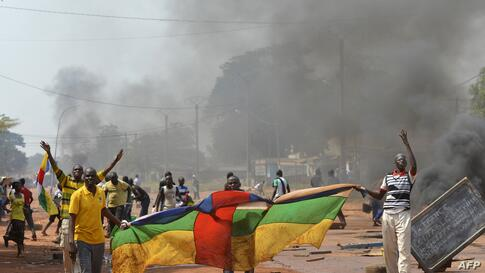 """People hold a Central African flag as they protest against the French """"Sangaris"""" intervention in the Galabadia neighborhood close to President Michel Djotodia's private house in the eigth district of Bangui."""