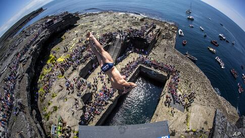 In this handout photo made available by Red Bull, David Colturi of the USA dives from the 28-meter platform at the Serpent's Lair during the third stop of the Red Bull Cliff Diving World Series at Inis Mor, Aran Islands, Ireland, June 29, 2014