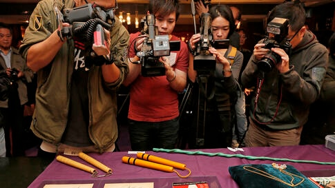 The late action film actor Bruce Lee's most iconic martial arts weapons, including a pair of yellow lacquered wooden nunchaku, second from left, are displayed during an auction preview in Hong Kong.