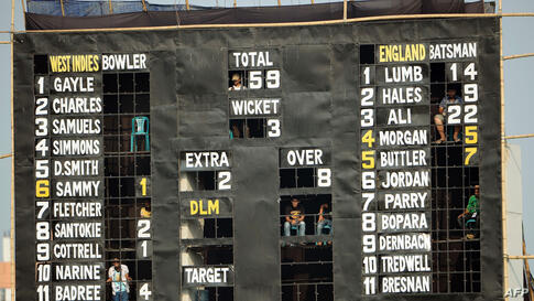 Bangladesh spectators sit inside a scoreboard as they watch the ICC World Twenty20 cricket tournament warm-up match between England and the West Indies at the Khan Shaheb Osman Ali Stadium in Fatullah on the outskirts of Dhaka.