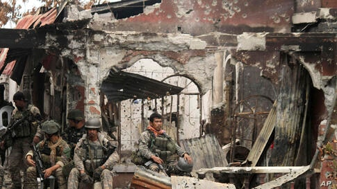 Government troops rest amidst the ruins at the site of a three-week standoff with Muslim rebels in Zamboanga City, southern Philippines.