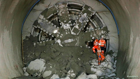 "Crossrail workers climb out from ""Victoria"", a tunnel boring machine after breaking through at Whitechapel underground station in London. Crossrail is the largest infrastructure project in Europe and will provide a new link across London which is due t..."