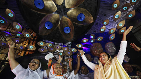Widows sing and dance inside a marquee where an idol of Hindu goddess Durga is installed ahead of the Durga Puja festival in Kolkata, India.