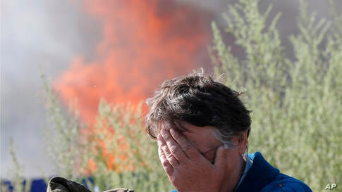 A woman cries near her burning house after shelling in the city of Slovyansk, Donetsk Region, eastern Ukraine. Residential areas came under shelling from government forces.