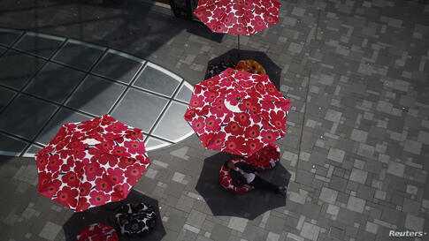 A man takes a nap on a cushion which is displayed as a promotional event of a fashion brand at a shopping mall in Beijing. Temperatures reached 37 degrees Celsius (98.6 F) since it hit a record high of around 40 degrees Celsius (104 F) Thursday, the hi...