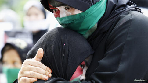 A Filipino Muslim woman, with colors of Palestinian flag painted on her face, cries as she embraces her child during a rally held by the Anak Mindanao (Children of Mindanao) Party List group outside the Israeli embassy in Taguig, Metro Manila, Philippi...