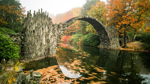 Fog hangs over trees in autumnal colors and the so-called Rakotzbruecke bridge of the Rhododendronpark Kromlau landscaped park in Kromlau, eastern Germany, Oct. 27, 2015.