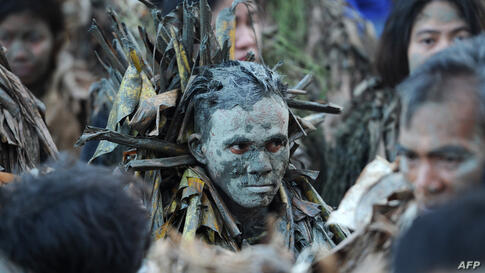 "Devotees covered in mud and wearing costumes made from banana leaves attend mass as they take part in a religious festival in honor of St. John the Baptist, also known locally as the ""mud people"" festival in Aliaga, Nueva Ecija province, north of Manil..."