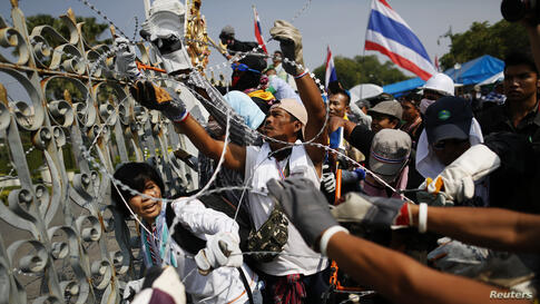Anti-government protesters in Bangkok, Thailand remove barbed wire before a small group of them briefly entered the compound of the prime minister's office, known as the Government House.