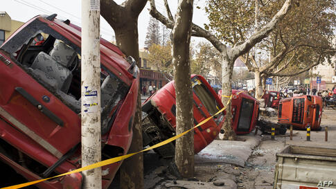 Damaged vehicles lie by a street after an oil pipeline exploded, killing at least 35 people, ripping roads apart, turning cars over and sending thick black smoke billowing over the city of Qingdao, east China's Shandong province.