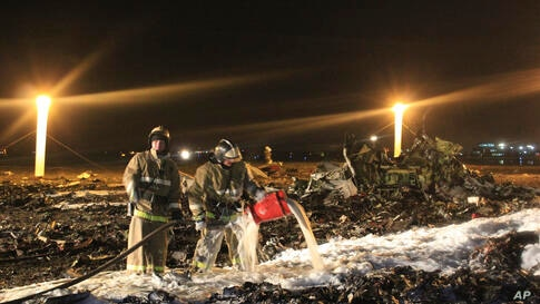 In this photo provided by Russian Emergency Situations Ministry, fire fighters and rescuers work at the crash site of a Russian passenger airliner near Kazan, the capital of the Tatarstan republic, about 720 kilometers (450 miles) east of Moscow, Nov. ...