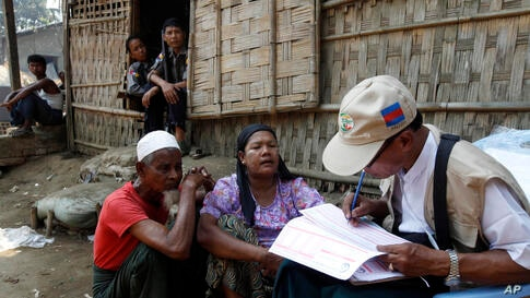 A census enumerator, right, collects information from a Muslim family as policemen provide security at Thae Chaung village in Sittwe, Rakhine State, western Burma. Enumerators fanned out across the country for a census that has been widely criticized f...