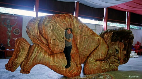 Swiss artist Dave Pflugi shows the shape of his sculpture named 'The Seeds of Victory' in Rio de Janeiro, Brazil.