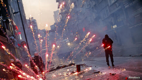 Fireworks thrown by anti-government protesters explode behind riot policemen near central Taksim square in Istanbul. Turkish police fired tear gas and water cannon to push back thousands of demonstrators during a protest triggered by the death of a tee...