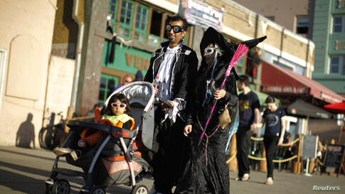 A family walks along Venice Boardwalk in their Halloween costumes in Venice, Los Angeles, California, Oct. 31, 2013.