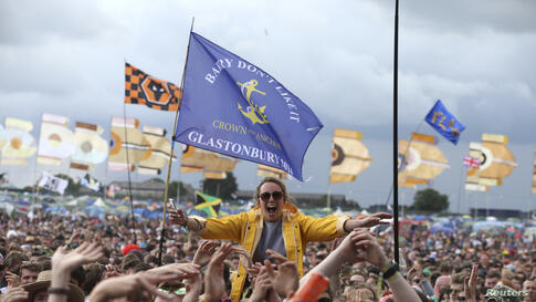 A festival-goer cheers in front of the Other Stage at Worthy Farm in Somerset, Great Britain, during the Glastonbury Festival.