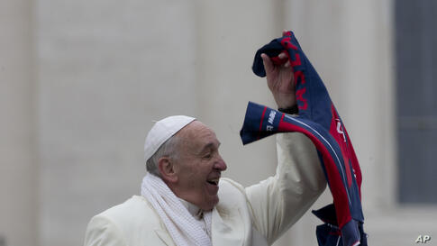 Pope Francis grabs a shirt thrown to him by faithful as he leaves at the end of his weekly general audience in St. Peter's Square at the Vatican.