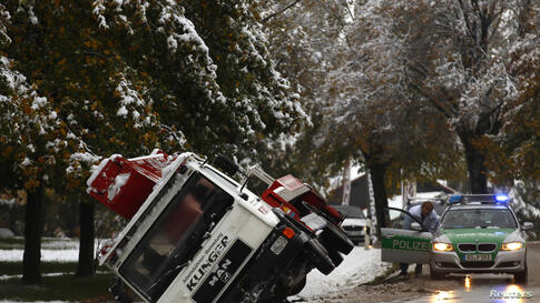 A toppled truck lies in a ditch in front of a police car in Murnau after heavy snow fall in southern Germany.