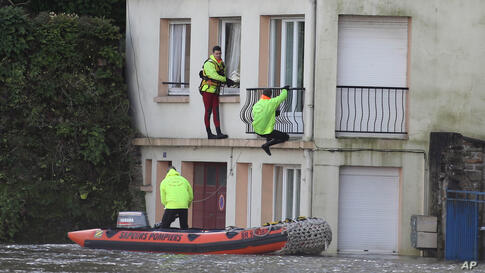 Rescuers secure houses in the center of Quimperle, western France, which has been flooded by the Laita river. Floods caused by heavy rains left the streets of some coastal towns underwater.