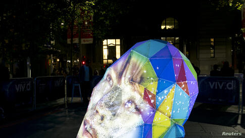 A woman's face is projected onto an art sculpture on the third night of the Vivid Sydney light and music festival, Australia.