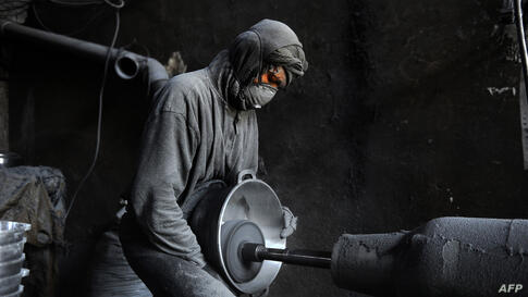 An Afghan laborer polishes a metal pot at an aluminium workshop in Herat.