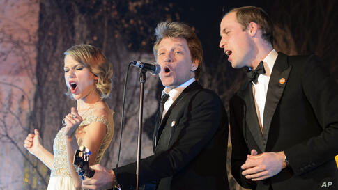 Britain's Prince William, the Duke of Cambridge, right, sings with U.S. singers Taylor Swift, left, and Jon Bon Jovi at the Centrepoint Gala Dinner at Kensington Palace in London, Nov. 26, 2013. Centrepoint is a charity supporting homeless young people...